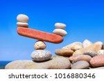 Small photo of Symbolic scales from stones. The disturbed equilibrium. Imbalance concept