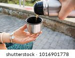 pouring tea from a thermos | Shutterstock . vector #1016901778