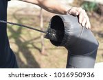 man cleaning chimney pipe... | Shutterstock . vector #1016950936