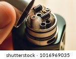 Small photo of Rebuildable dripping atomizer or RDA for vaping or e-cigarette with coil and cotton stripes wetted with e-liquid, modern vape device for quit smoking, macro photo with selective focus