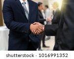 business shaking hands of... | Shutterstock . vector #1016991352