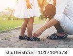 mother tying shoe  little girl... | Shutterstock . vector #1017104578