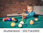 little boy playing billiard ... | Shutterstock . vector #1017161002