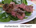 Beef Steak Skewers Over Spinach - stock photo