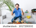 Small photo of Young man sport fan watching match in a blue t-shirt victory