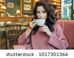 woman drinking coffee in a cafe | Shutterstock . vector #1017301366