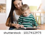 Young Mother Reads Book To...