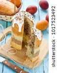 Small photo of Layered chocolate Easter cake kulich or paska cut on dining table with colored Easter eggs