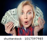 Small photo of Beautiful young blonde is a lucky winner, she is holding a pile of money, she is surprised and can't believe it, she is happy to win one million dollar jackpot, now she is rich.