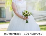 bride with a bouquet in the park | Shutterstock . vector #1017609052