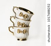 three white cups with a gold... | Shutterstock . vector #1017688252