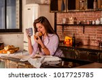 the girl drinks coffee with a... | Shutterstock . vector #1017725785