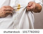 Small photo of Frustrated person pointing to spilled curry stain on white shirt