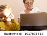 Small photo of the child is in shock because parents and grandmother spend the whole day at the computer. Dependence on social networks. Poor performance of parental responsibilities, the upbringing of children