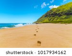 Small photo of Footprints lead off into the horizon on a secluded beach on the island of Oahu, Hawaii.