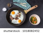two fried eggs with bacon and... | Shutterstock . vector #1018082452