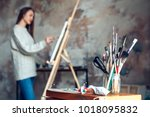 young woman artist painting at... | Shutterstock . vector #1018095832