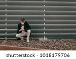 Small photo of Businessman crouched using the mobile in front of a building