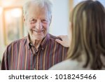 Small photo of Senior man smiling as a family member comforts him in his retirement home.