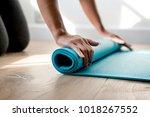 woman rolling yoga mat | Shutterstock . vector #1018267552