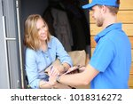 smiling delivery man in blue... | Shutterstock . vector #1018316272