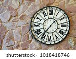Small photo of Old rusty and scratched on surface of metal on vintage Roman alphabet clock on stone wall