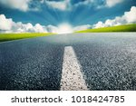 empty street and sunrise at the ... | Shutterstock . vector #1018424785