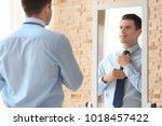 young businessman looking at... | Shutterstock . vector #1018457422