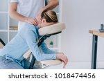 masseur doing seated neck... | Shutterstock . vector #1018474456