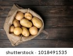 sack of fresh raw potatoes on... | Shutterstock . vector #1018491535