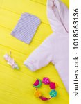 Small photo of Concept of pink baby cloth with necessities. Cropped vertical image of baby cotton jumpsuit, stripped hat, rattle and pills.
