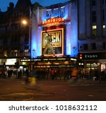 Small photo of London, United Kingdom - March 08 2004: Traffic passes under the Statue of Freddie Mercury outside the Dominion Theatre during the run of Queen Musical We Will Rock You