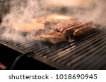 grilled stake and sausages on... | Shutterstock . vector #1018690945