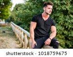 attractive muscular man in city ... | Shutterstock . vector #1018759675