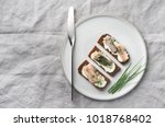 Stock photo toast with herring and green onion on rye bread on a ceramic gray plate steel knife linen 1018768402