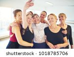 Small photo of Mixed age group of smiling women standing arm in arm together in a dance studio taking a selfie