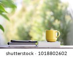 yellow cup with books on wooden ... | Shutterstock . vector #1018802602