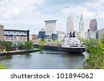 A Great Lakes self unloading bulk carrier ship negotiates a sharp curve in the Cuyahoga River with the downtown Cleveland, Ohio skyline in the background - stock photo