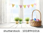 Small photo of Easter table background of free space for your product. Blurred window background. Eggs and flowers decoration.