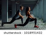 young couple stretching legs in ... | Shutterstock . vector #1018951432