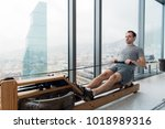 man working out on row machine... | Shutterstock . vector #1018989316