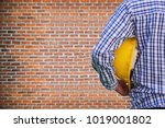Small photo of engineer or worker holding in hand helmet for workers security on brickwall background