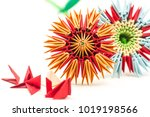 Small photo of couple of module origami paper flowers with red modules craft isolated on white background