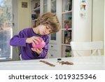 little boy putting coins into... | Shutterstock . vector #1019325346