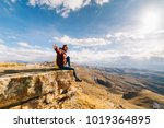 happy woman tourist sits on a... | Shutterstock . vector #1019364895