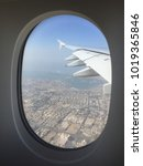 Small photo of Dubai city in the morning views from aeroplane window during take off