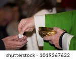 Small photo of hands of a priest who give communion during mass