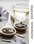 mud-mask, scrub creme,massage oil surrounded by petals - stock photo