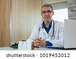 mature male doctor sitting at... | Shutterstock . vector #1019452012