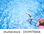 Small photo of Little boy enjoying safety at swimming pool. He wears armband floats and float belt